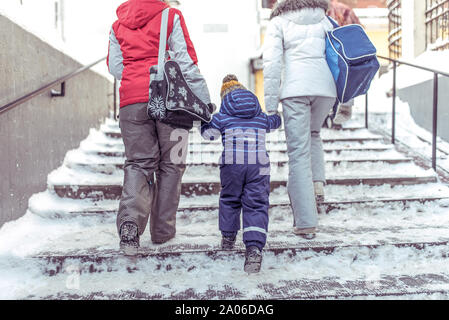 woman's mother walks down street winter step snow, with girlfriend small child, boy or girl 3-5 years old, view from back, background road - Stock Photo