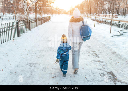 Woman mother walks down street winter, with small child, boy or girl 3-5 years old, view from rear, background road snowdrifts, returns kindergarten - Stock Photo
