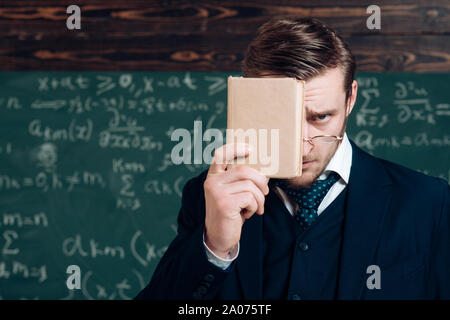 Young man in suit covering his face with book. Closeup portrait of young blond aristocrat with stylish hair and beard. - Stock Photo
