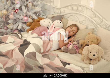 Christmas dreams. Sleeping child. Little child sleep at Christmas tree. Little girl lying in bed with toys. Cute girl fell asleep after Christmas night. Peaceful sleep and rest on winter holidays. - Stock Photo