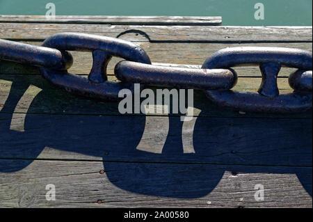 A heavy metal anchor chain lies on a wooden wharf - Stock Photo