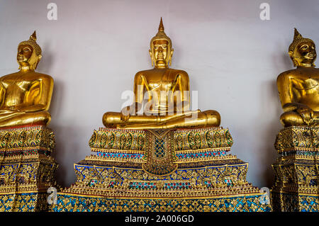 Sitting golden Buddhas Golden statue of Buddha sitting in meditation on beautifully decorated pedestal. Wat Pho, Temple of Reclining Buddha - Stock Photo