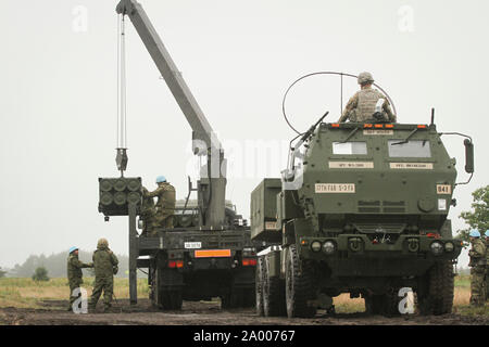 190916-A-FJ530-820 Soldiers assigned to the Western Army Field Artillery of the Japan Ground Self-Defense Force observe and facilitate reload operations on the U.S. Army High Mobility Artillery Rocket System at Yausubetsu Training Area, Japan, Sept. 16. Bravo Battery, 5th Battalion 3rd Field Artillery deployed for the first time a HIMARS to Japan in support of bilateral exercise Orient Shield 2019. The HIMARS is a key capability for the U.S. Army's Multi Domain Task Force increasing the lethality of the MDTF. (U.S. Army photo by Capt. Rachael Jeffcoat) - Stock Photo