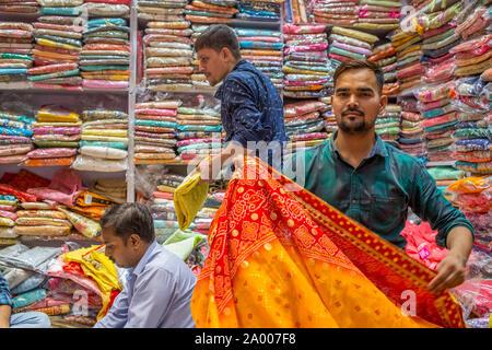A Indian sari salesman in a local shop in Chandni Chowk market in New Delhi, India - Stock Photo