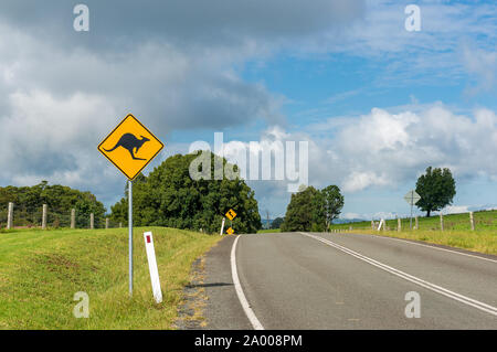 Australian outback road with kangaroo road sign. Country road in rural Australia with kangaroo on the road warning road sign - Stock Photo
