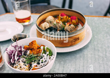 Pan-Asian food - vegetable salad bowl and different dim sums. Lunch for two with beer - Stock Photo