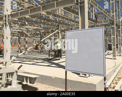 Object under construction stand at the construction site. Blank display board against prefabricated multi-storey building at the background