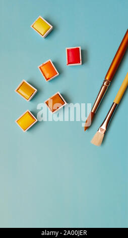 Paint brush and warm color palettes of red, orange and yellow, with blue background.