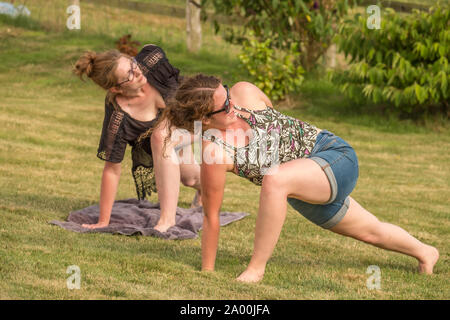 Two young women practice their yoga moves by stretching on a grass lawn on a sunny, fine summer day in England, UK - Stock Photo