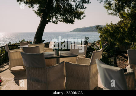 wicker chairs and tables in a summer cafe with sea views. Restaurant sea terrace - Stock Photo