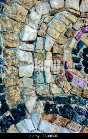 Fragment of the wall of small colored stones. Texture of stone. Beautiful natural colorful background. Blur, soft focus