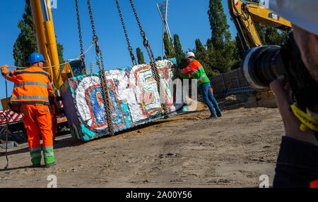 Berlin, Germany. 19th Sep, 2019. A crane lifts a granite block in the Mauerpark back to its place. The granite block and a tank barrier had been moved for the work of the water companies on the reservoir canal, which is to store waste water. Credit: Andreas Gora/dpa/Alamy Live News - Stock Photo