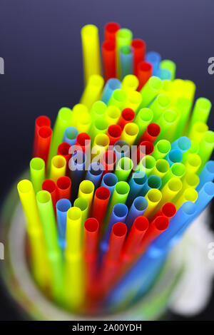 colored plastic cocktail tubes standing in a glass - Stock Photo