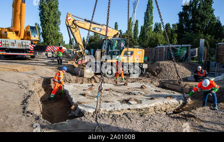 Berlin, Germany. 19th Sep, 2019. A crane lifts a tank barrier back into place in the Mauerpark. A granite block and the tank barrier had been moved for the work of the water companies on the reservoir canal, which is to store waste water. Credit: Andreas Gora/dpa/Alamy Live News - Stock Photo