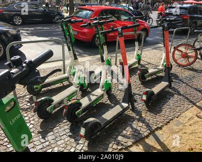 BERLIN - SEPTEMBER 08, 2019: Many Electric E-Scooters of different Ride Sharing Companies parked chaotically on a sidewalk in Berlin close to the Bran - Stock Photo