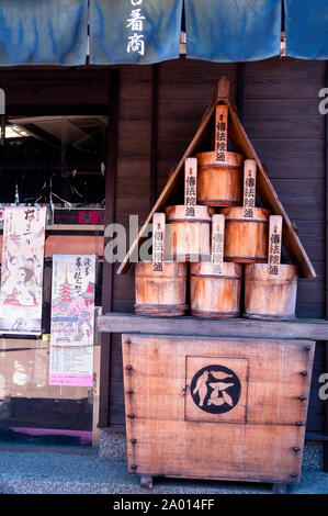 Traditional Japanese wooden buckets displayed under Noren curtains in Tokyo, Japan.