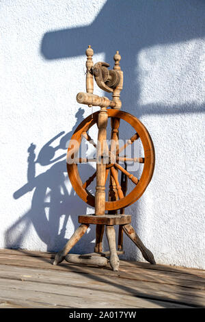 Wooden spinning wheel in the morning sun against a white wall closeup - Stock Photo