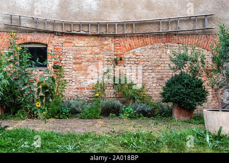 Vegetable & herb garden against a rustic brick barn wall in the Uckermark area, Brandenburg, Germany - Stock Photo