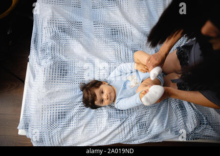 Pregnant Mother laying with her baby son on the bedroom bed playing and having fun - Asian mixed ethnicity child Boy wearing blue body shirt with