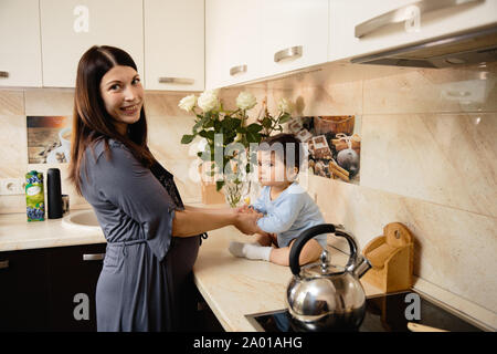 Pregnant Mother cooking with her baby son in the kitchen and having fun - Asian mixed ethnicity child Boy wearing blue body shirt with smiling bear - Stock Photo