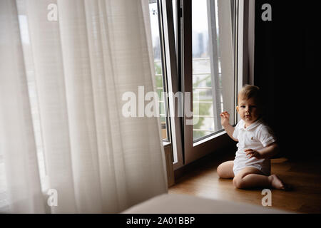 Young blonde mother having quality time with her baby boy son at family home flat - Wearing black budoir dress costume sleeping gown - Stock Photo