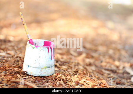single paintbrush in a white paint tub. Bush, mulch, wood chip background. Creative potential concept or theme. Bright fluorescent fluro pink magenta - Stock Photo