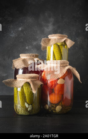 Canned fruits and vegetables, plum, cucumber, tomato in glass jars on dark wooden board. Various types of fermented. Vertical orientation. - Stock Photo