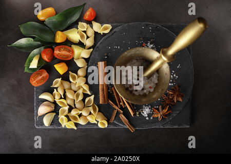 Pasta shells on black stone. Tomatoes and bay leaves with allspice and sea salt. - Stock Photo