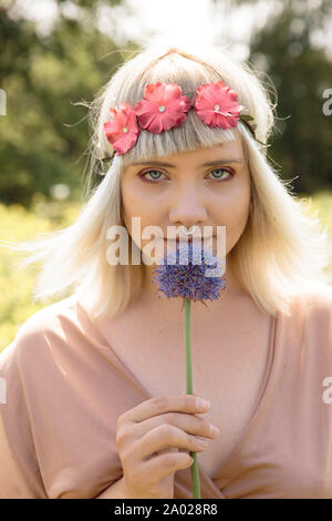 Young blonde hippie woman with onion and flower band