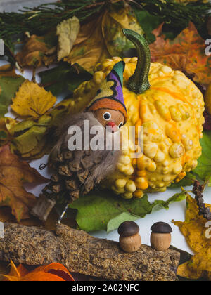 Autumn background with colorful mixed leaves, pumpkin, berries, cydonia, physalis and fairytale gnome and mushrooms from wood. Mockup for seasonal off - Stock Photo