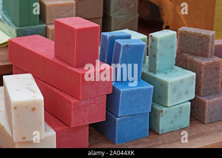 Bars of artisanal soap of different colors sold on street market. - Stock Photo