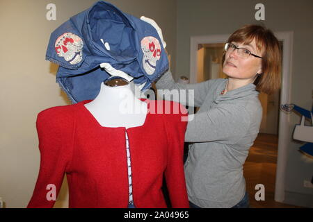 19 September 2019, Saxony, Bautzen: Exhibition curator Andrea Paulick attaches a modern hood by Sarah Gwiszcz to the exhibition 'Sorbian Street Style' at the Sorbian Museum. The traditional costumes disappear more and more from the everyday life of Lusatia. The Sorbian Museum Bautzen is now showing how traditional patterns, colours, cuts and shapes can be turned into wearable everyday fashion. (to 'Exhibition 'Sorbian Street Style': Creative inspirations from the chest') Photo: Miriam Schönbach/dpa-Zentralbild/ZB - Stock Photo