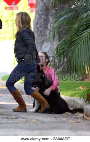 When Jennifer Aniston spotted a dog running loose along busy Sunset Blvd. she knew she had to do something quick or the dog, a husky, was not long for this world. So Jen turned off on to a side street just as the dog did. She quickly pulled to the curb, hopped out of her car and coaxed the dog to stand still and grabbed him. The dog wasn't wearing a collar. An unidentified woman (in pink) stopped after Jen and helped her detain the pooch while a photographer, who saw what house the dog ran from, went to alert the owner. Turns out a maintenance worker had left a gate open at the house in - Stock Photo