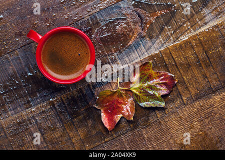 Red cup with  coffee and  autumn leaves on  old  wet wooden table.  Flat lay - Stock Photo