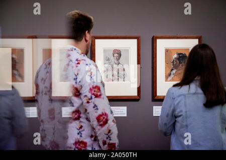 Berlin, Germany. 19th Sep, 2019. A man and a woman are watching the special exhibition 'Menzel. Maler auf Papier' in the Kupferstichkabinett in the Kulturforum at Potsdamer Platz. The exhibition shows works by the painter Adolph von Menzel. (Effect of reflection in display case) Credit: Christoph Soeder/dpa/Alamy Live News - Stock Photo