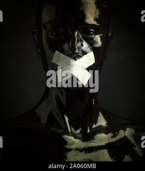 Black mannequin with tape over its mouth in front of black background - Stock Photo