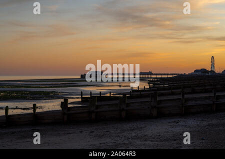 Worthing Pier at sunset with light reflecting in rock pools. - Stock Photo