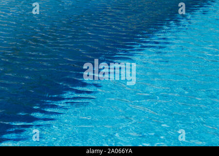 A two colored light and dark blue water with ripples and sunny reflections in a swimming pool. - Stock Photo