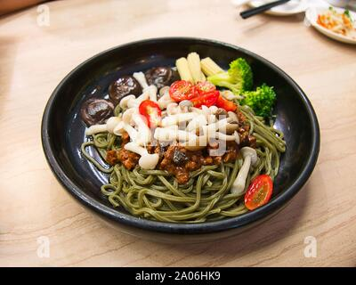 Vegetarian Matcha / green tea noodles with vegetables and savoury tofu sauce in black bowl on wooden table - Stock Photo