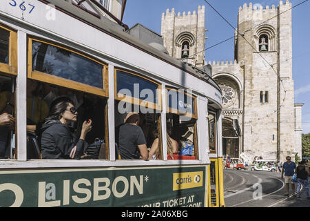 Lisbon, Portugal – august, 2019: tourists by tram passing in front of the cathedral at Alfama district - Stock Photo