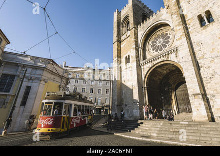 Lisbon, Portugal – august, 2019: tourist yellow tram passing by the cobblestone street in front of the cathedral at Alfama district - Stock Photo