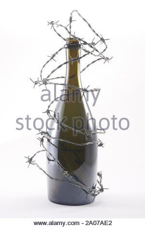Barbed wire blocks alcohol bottle. Isolated on white background. With copy space text. Studio Shot. - Stock Photo