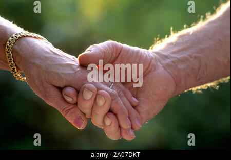 Two married seniors in love holding hands outdoors - Stock Photo
