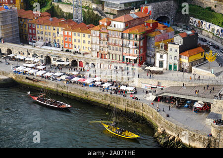 Porto, Portugal - December 2018: View from Luis I Bridge to the Ribeira area and the Douro River with two Rabelo boats. - Stock Photo