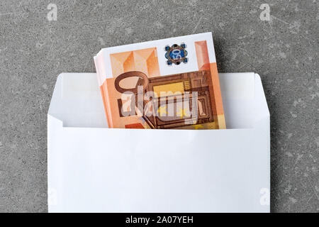 White envelope with a 50 euro bills. Stack of fifty euro notes in open mail envelopeon concrete. A euro banknotes folded in an envelope as a present