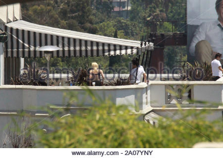 Hollywood, CA - Singer Lady Gaga hangs out with some fiends on the balcony of her room at the Chateau Marmont in Hollywood, showing off some skin wearing a black lace bra and black tights. At one point Gaga gives her male friend a big hug while her blonde gal pal sits on the ledge of the balcony. AKM-GSI July 9, 2012 - Stock Photo