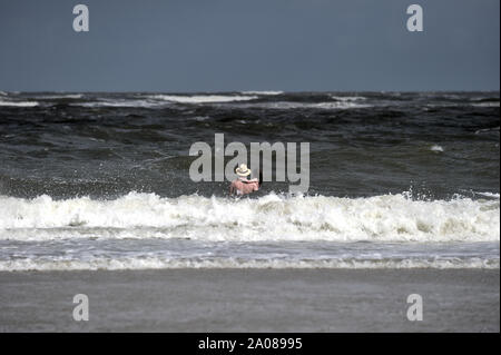 A man with a hat and a child in his arms is walking towards the waves (North Sea, Langeoog, Germany). - Stock Photo