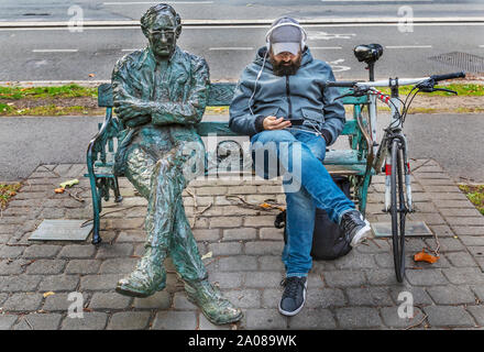 A man leisurely sits on a bench reading while sitting next to a metal sculpture of a man also sitting and relaxing on the bench. - Stock Photo