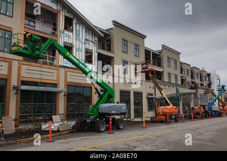 Several man-lifts being used on the exterior of a new building under construction in Steveston British Columbia Canada - Stock Photo
