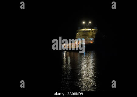 Borneo, Indonesia - July 2019: Maersk owned oil field support vessel standing by on an oil field by night - Stock Photo